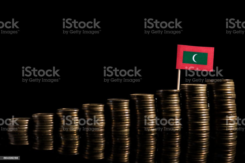 Maldives flag with lot of coins isolated on black background stock photo