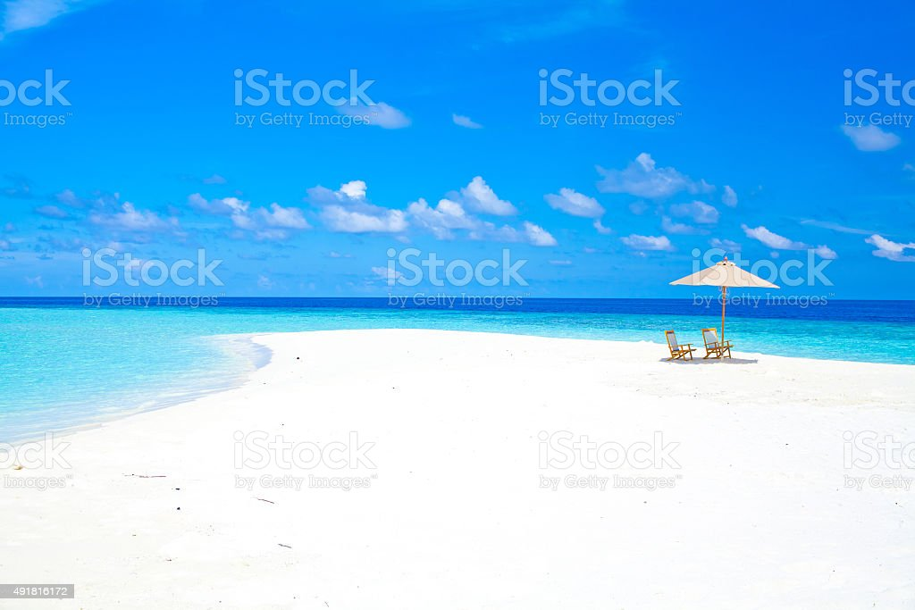 Maldives sandbank with umbrella and chairs stock photo