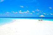 Maldives sandbank with umbrella and chairs