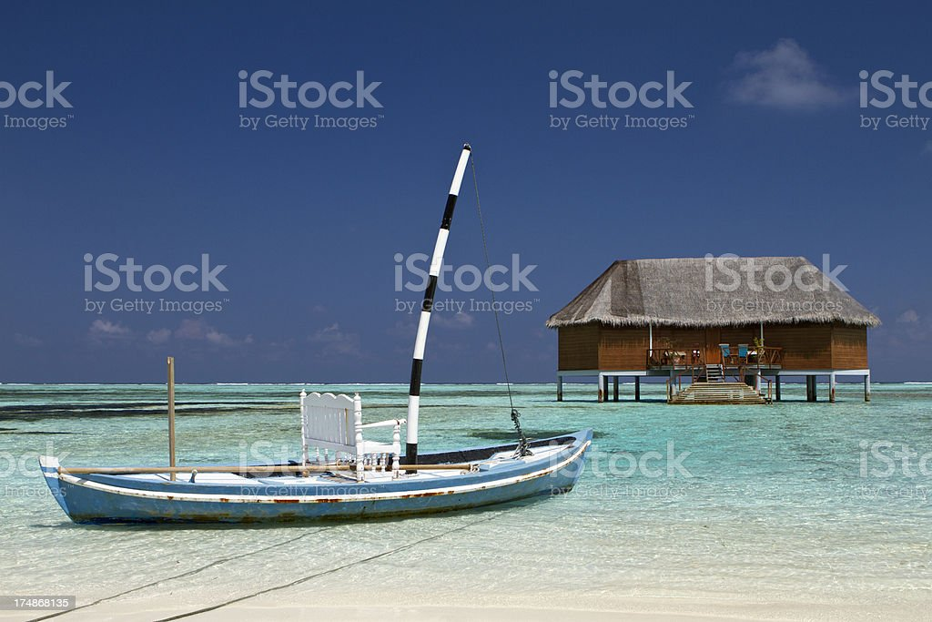 Maldives villa on stilt with wooden boat royalty-free stock photo