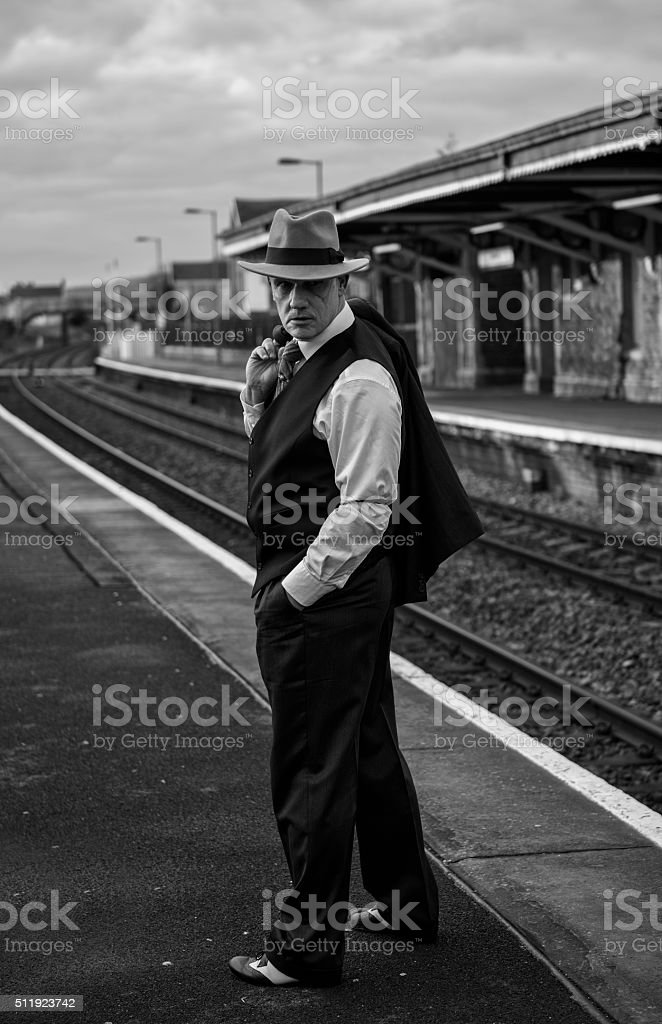 Male 1940s gangster charcater standing by train tracks. stock photo