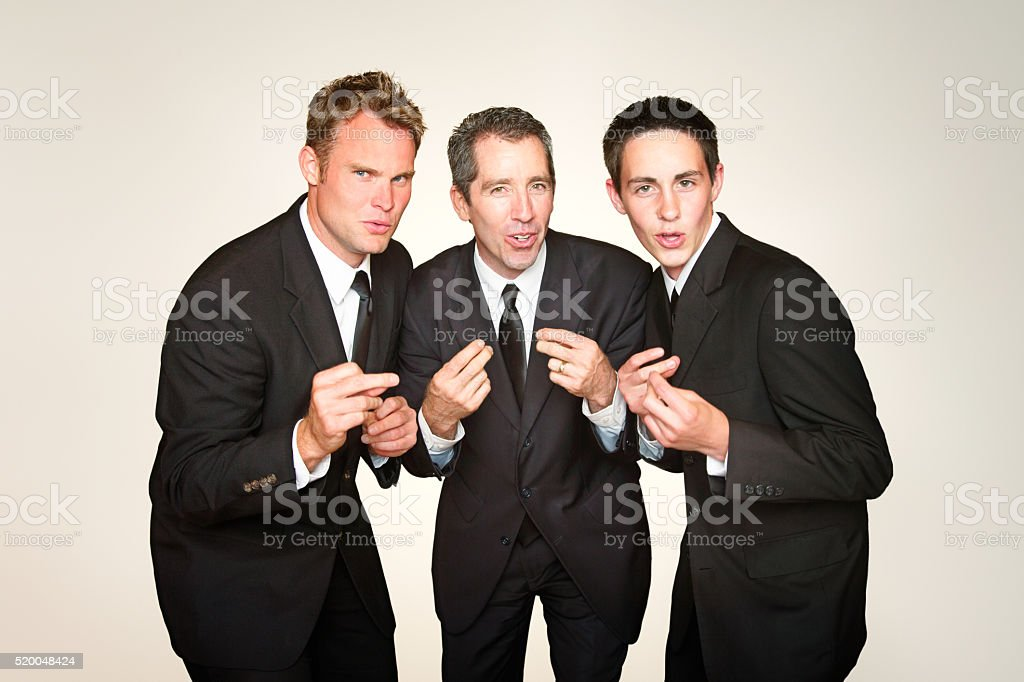 Male a capella trio in suits singing and snapping stock photo
