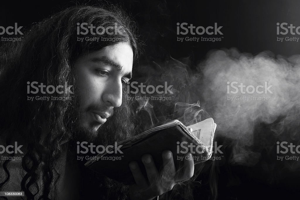 Male Alchemist Blowing Dust Off and Antique Book royalty-free stock photo