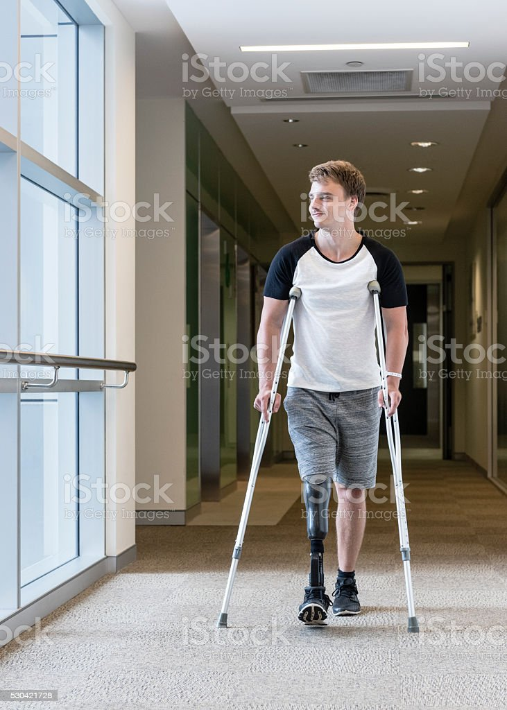 Male amputee with prosthetic leg in hospital corridor stock photo