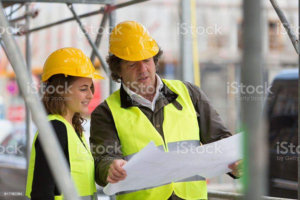 Male and female architects checking blueprints among scaffolding stock photo