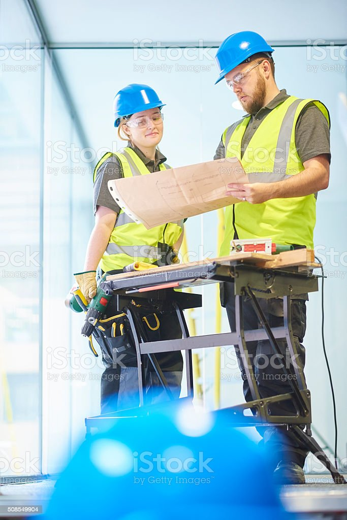 male and female carpenters checking the plans stock photo