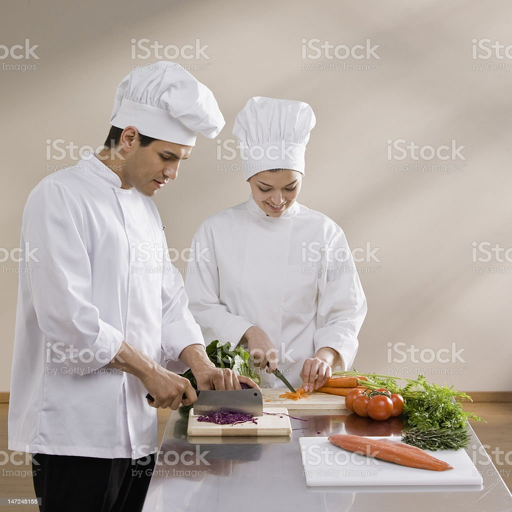 Male and female chef chopping vegetables royalty-free stock photo