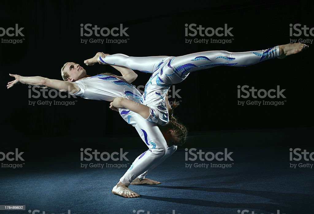 Male and female circus artists performing an acrobatic move stock photo