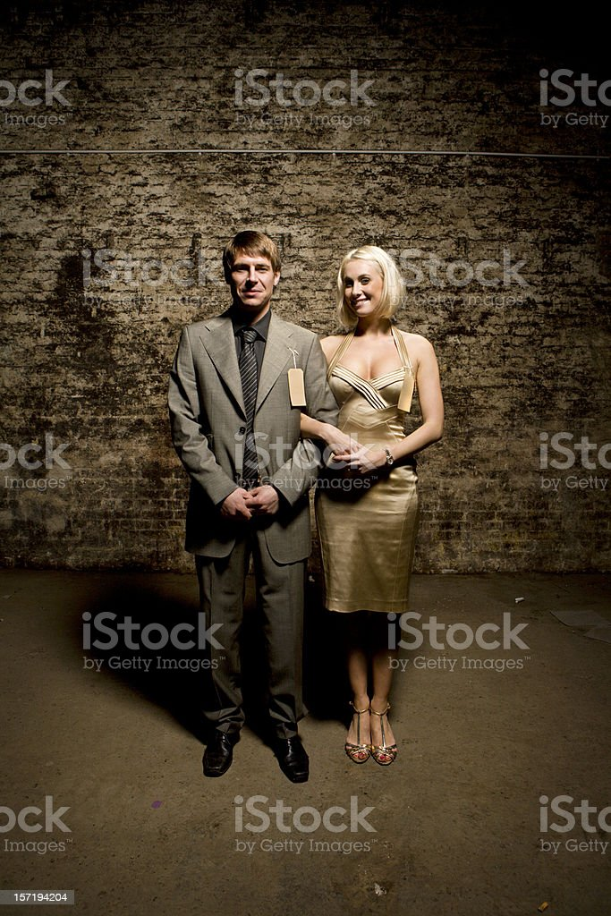 male and female couple wearing formalwear in front of bricks royalty-free stock photo