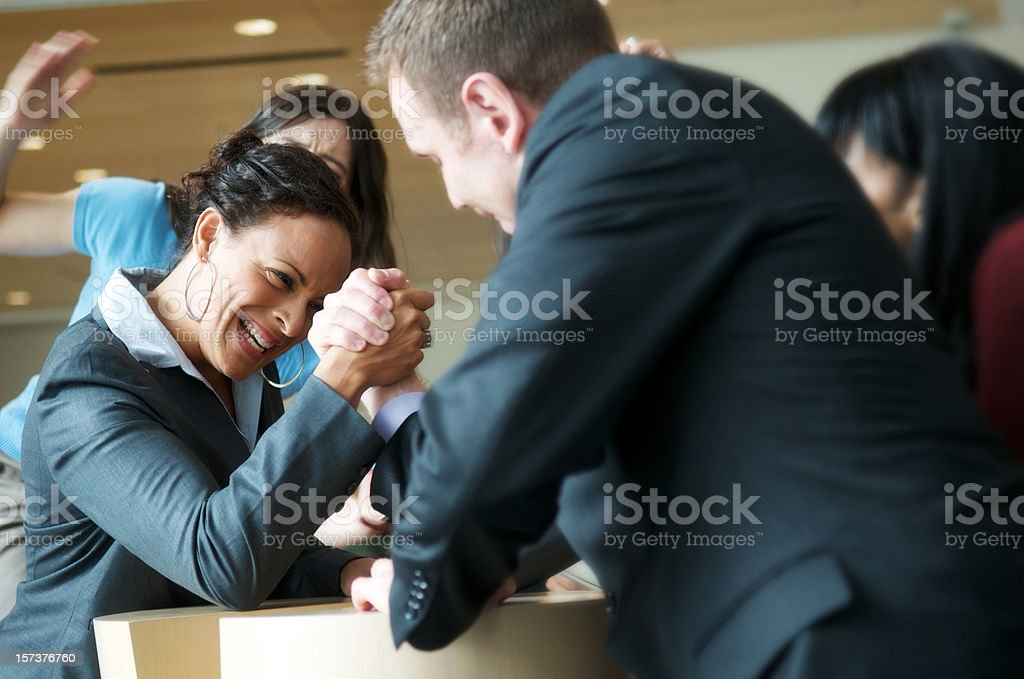 Male and female executive arm wrestling stock photo