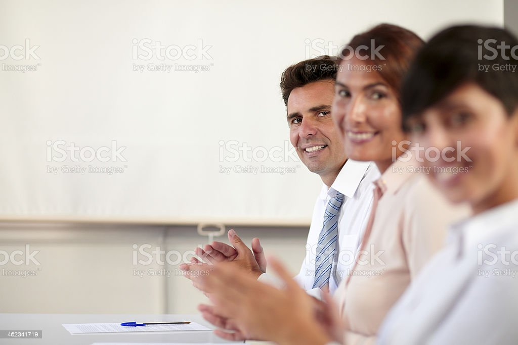Male and female executive smiling at you stock photo