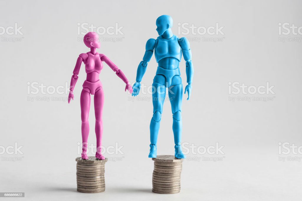 Male and female figurines holding hands looking at each other, standing on top of equal piles of coins. Income equality concept with copy space stock photo