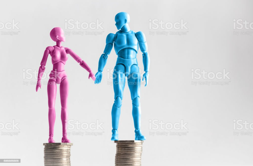 Male and female figurines holding hands looking at eachother, standing on top of equal piles of coins. Income equality concept with copy space stock photo