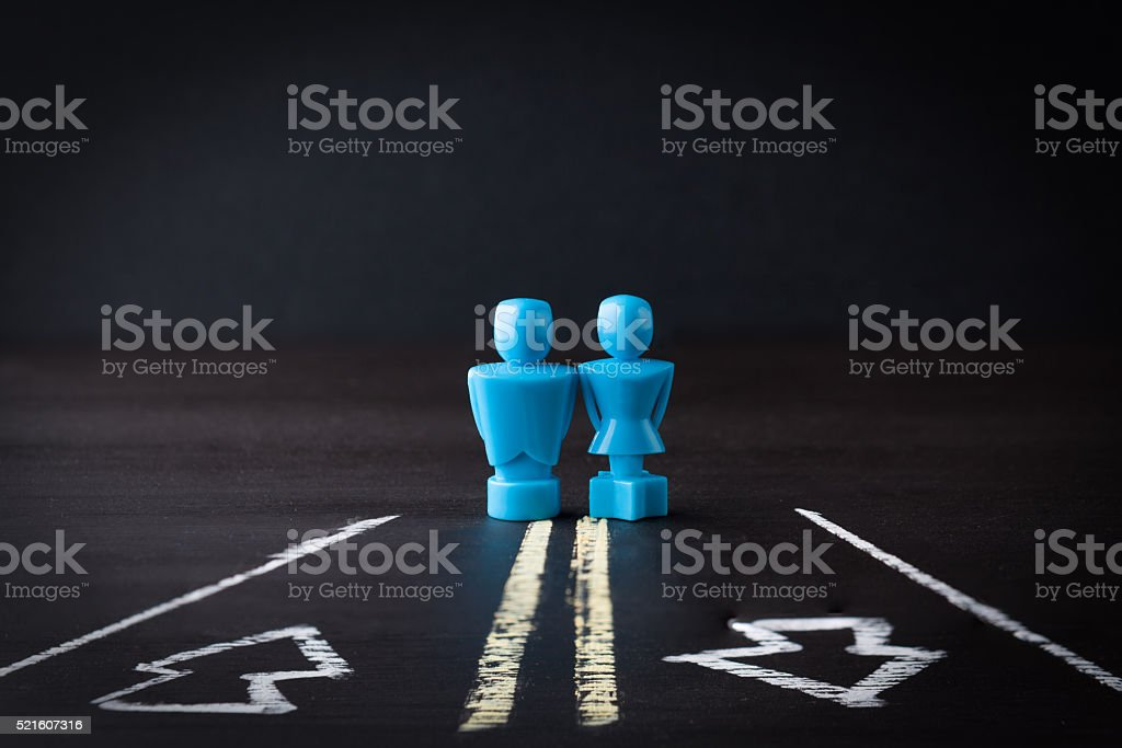 Male and female figurines on two way road stock photo