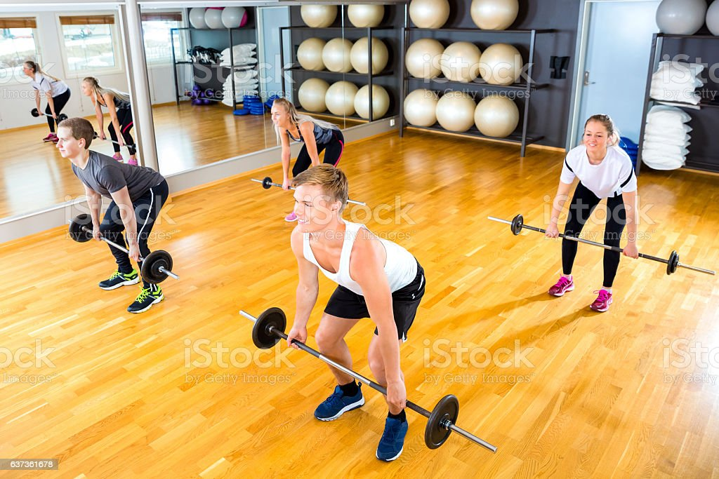 Male And Female Friends Exercising With Barbells In Gym stock photo