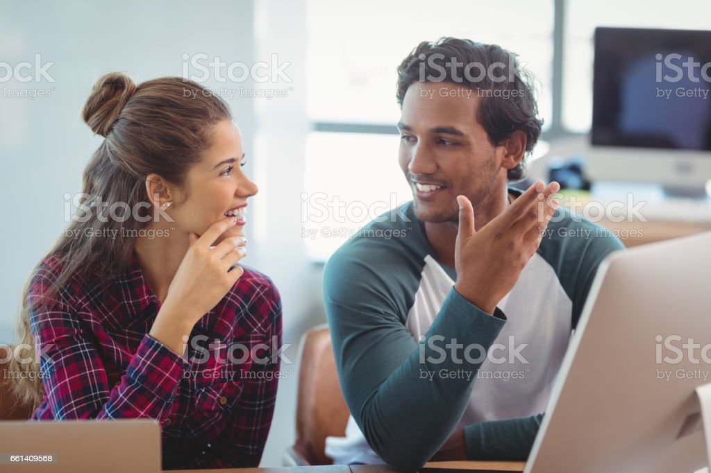 Male and female graphic designers interacting with each other at desk stock photo