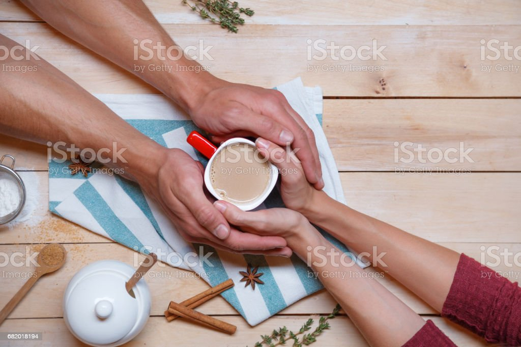 Male and female hands are holding a cup between them stock photo