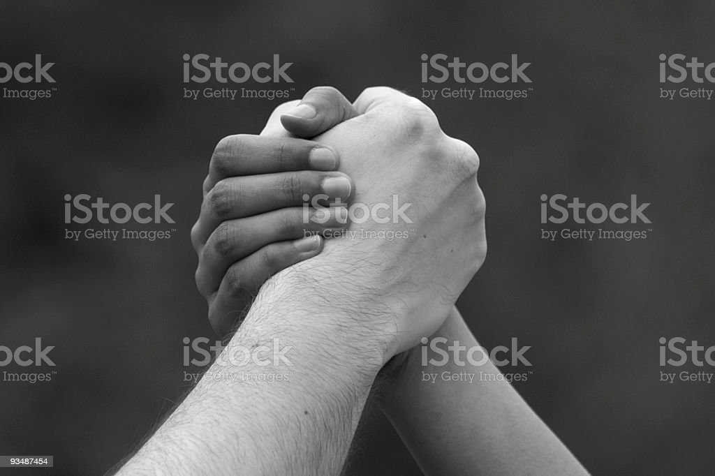 Male and female hands clasped, ethnicity concept, black & white stock photo