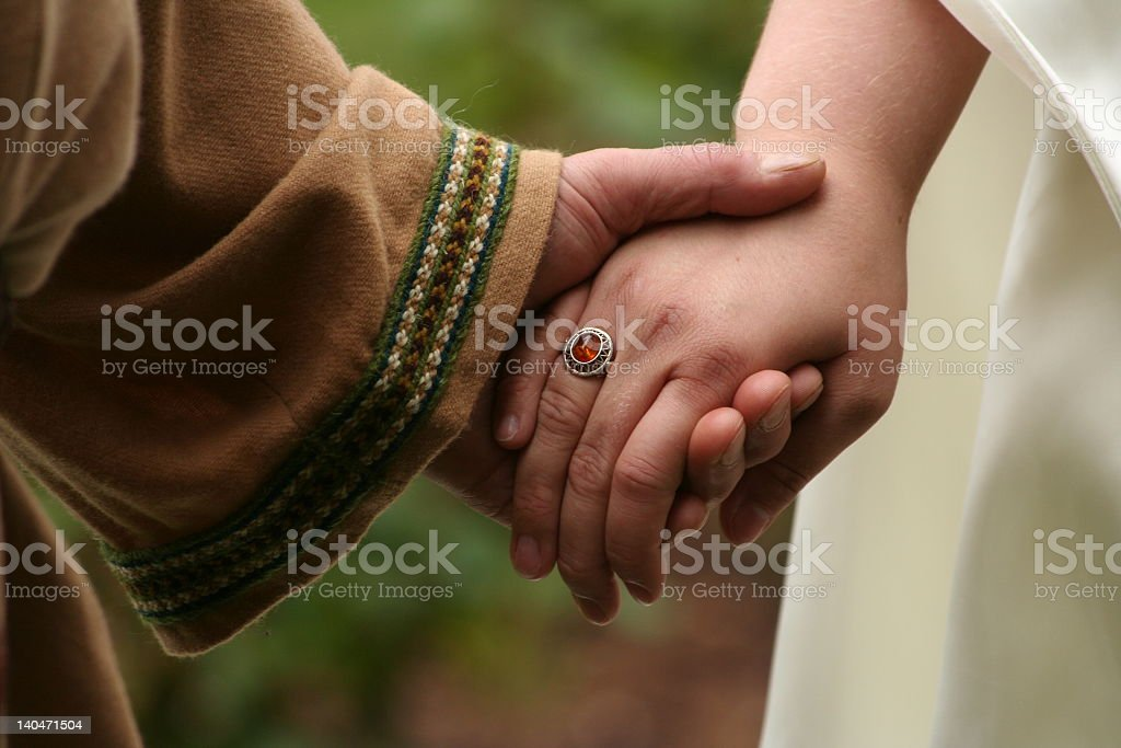 Male and female hands clasped in wedding ceremony stock photo
