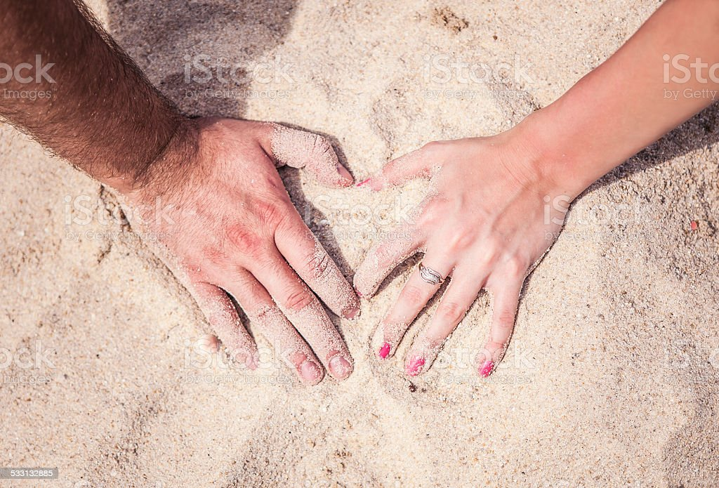 Male and female hands with rings on the sand stock photo