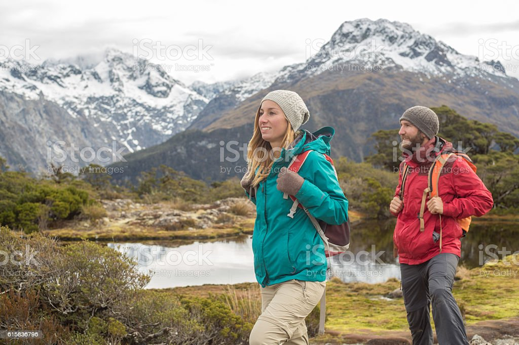 Male and female hiker on mountain trail stock photo