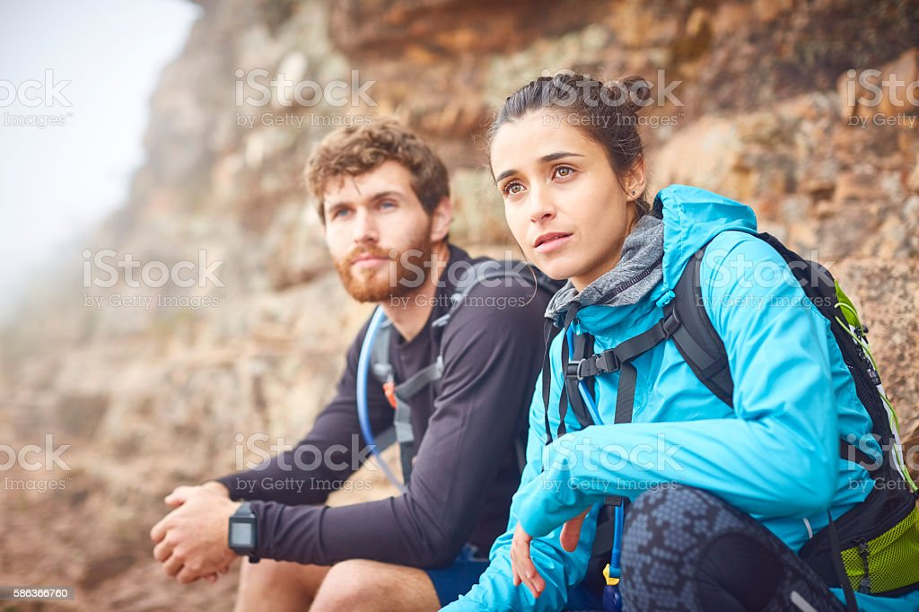 Male and female hikers looking away on mountain trail stock photo