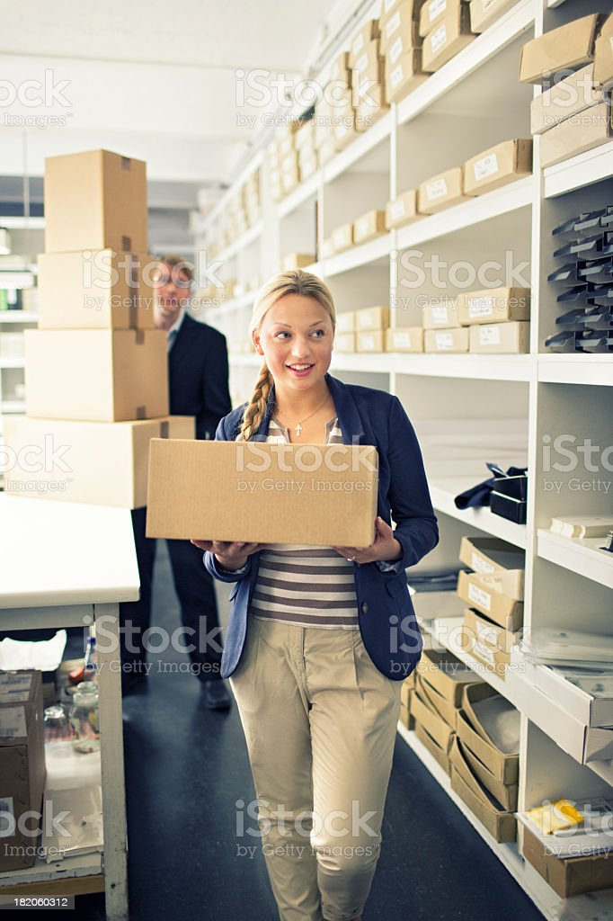 Male and female office worker carrying boxes stock photo