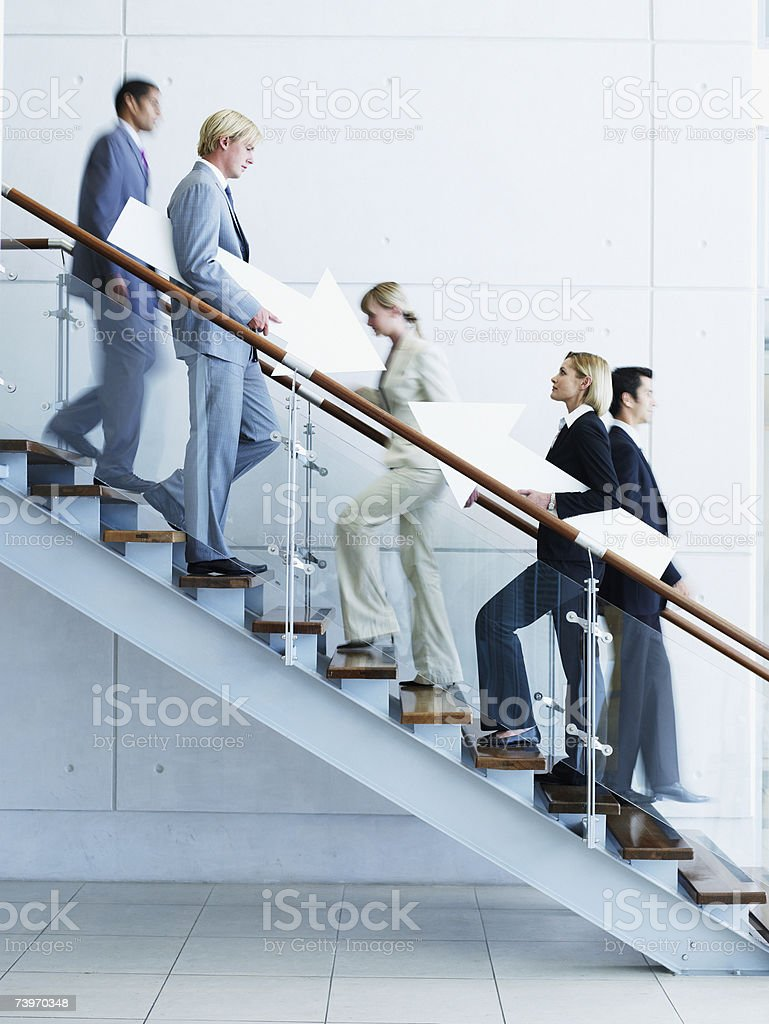 Male and female office workers on staircase holding arrow signs royalty-free stock photo