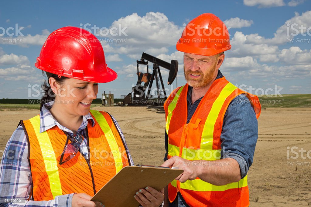 Male and Female Oil Worker in Conversation at a Pumpjack stock photo