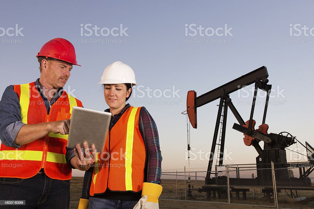 Male and Female Oil Workers stock photo