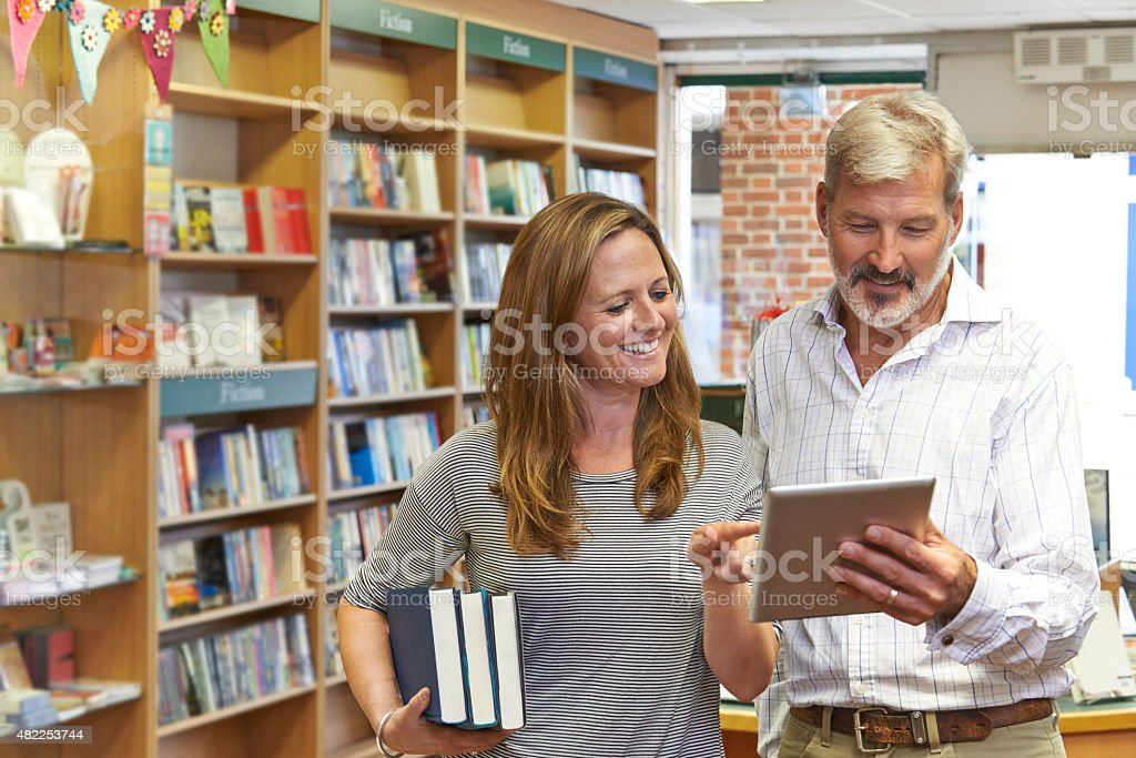 Male And Female Owners Of Bookstore Using Digital Tablet stock photo