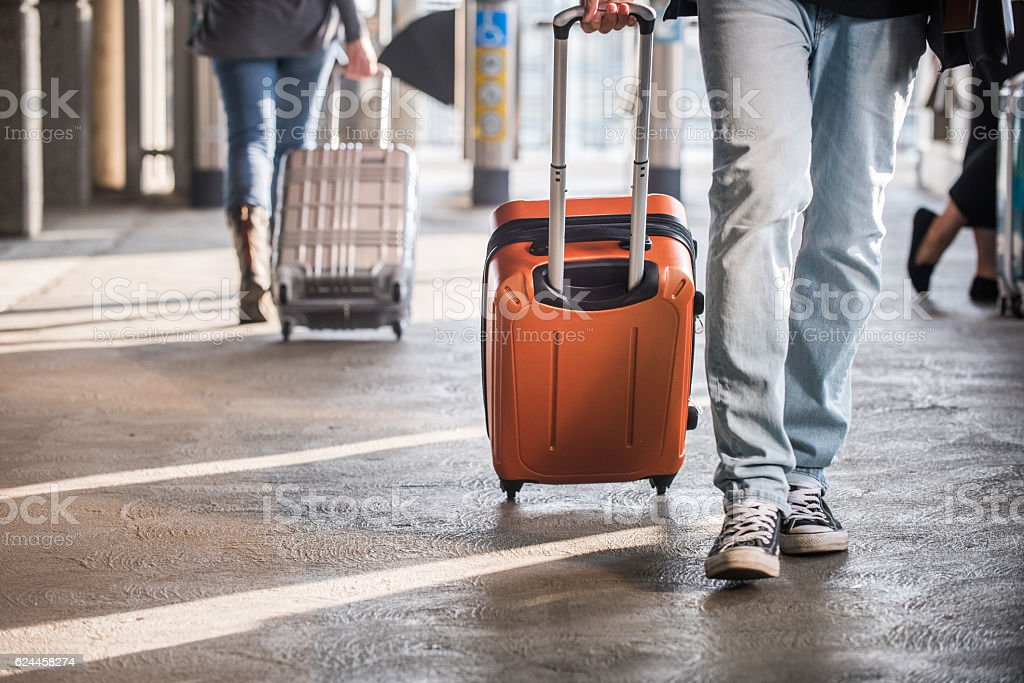 Male and Female Travelers Rolling Suitcases stock photo