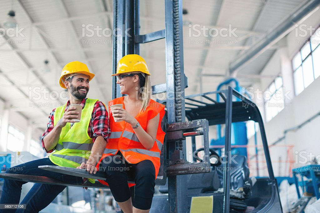 Male and female worker in factory having coffee break stock photo