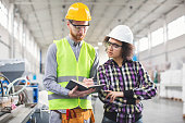 Male and female worker in factory taking notes