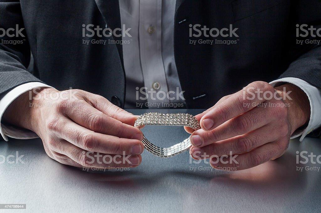 male appraiser's hands with diamond bracelet stock photo