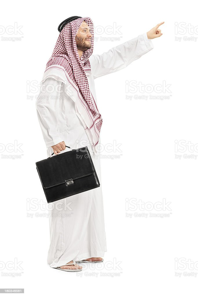 Male arab person holding a suitcase and pointing royalty-free stock photo
