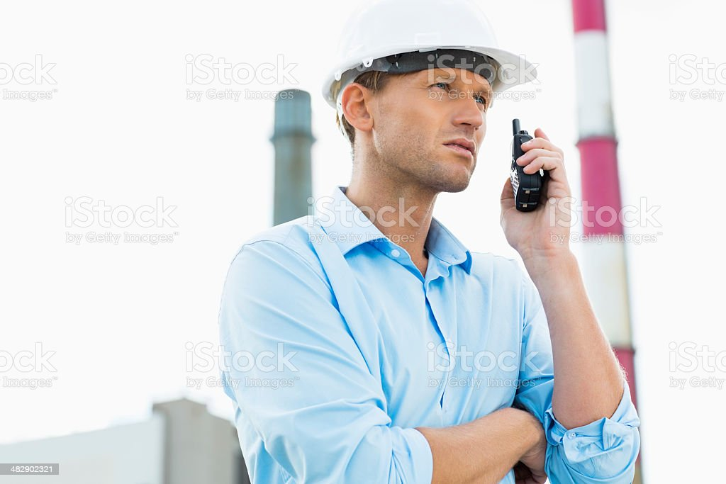Male architect communicating on walkie-talkie at site stock photo