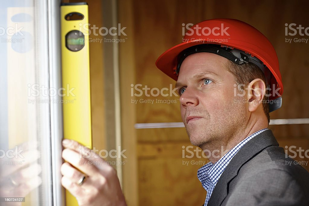 Male architect examining level at construction site royalty-free stock photo