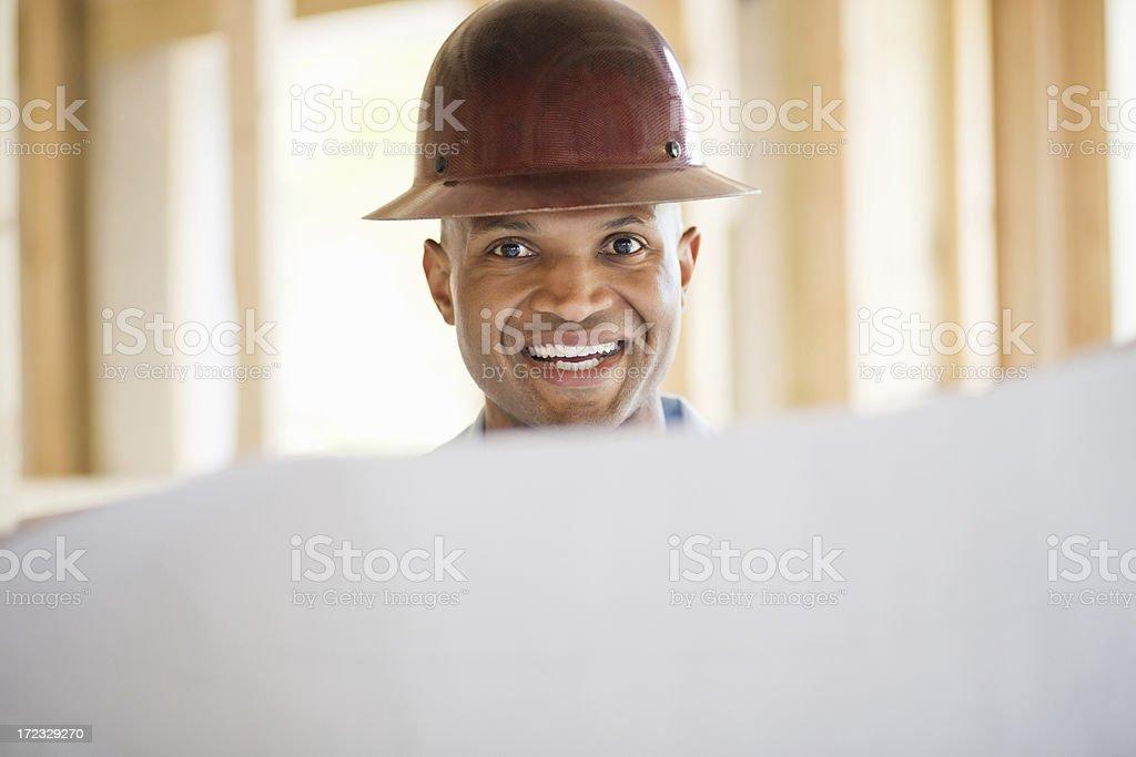 Male Architect Wearing Hardhat With Blueprint royalty-free stock photo