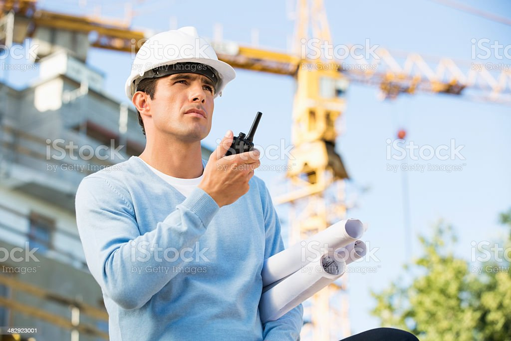 Male architect with blueprints using walkie-talkie at construction site stock photo