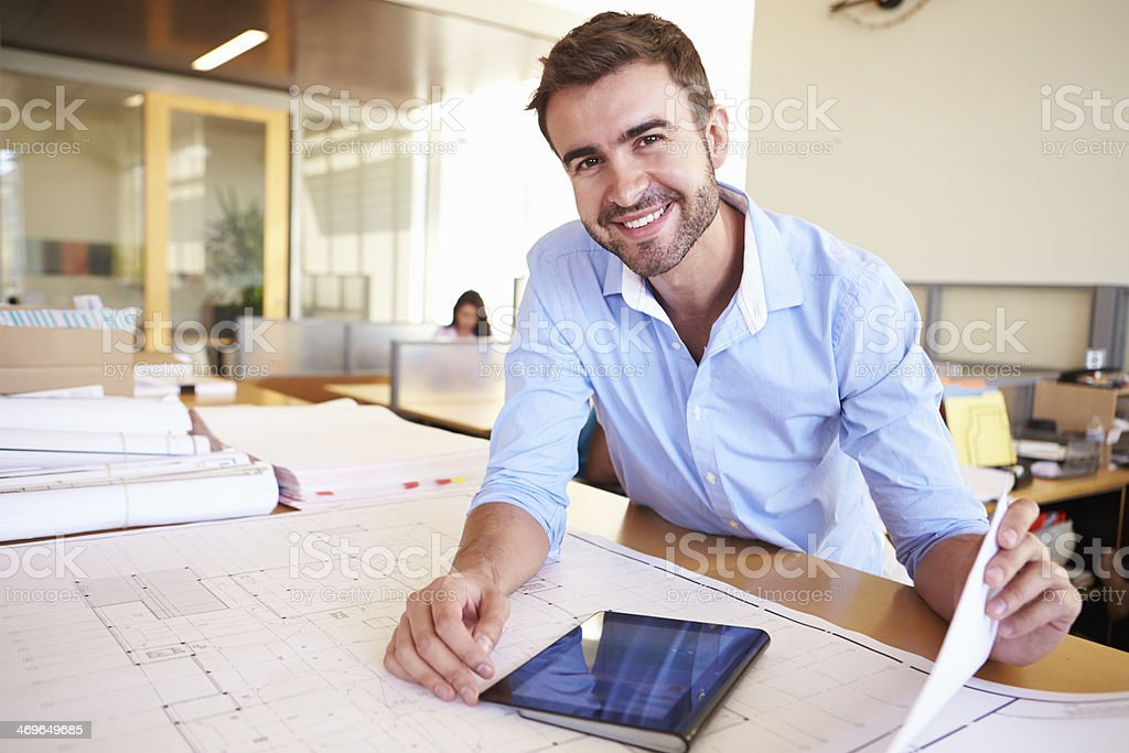 Male Architect With Digital Tablet Studying Plans In Office stock photo
