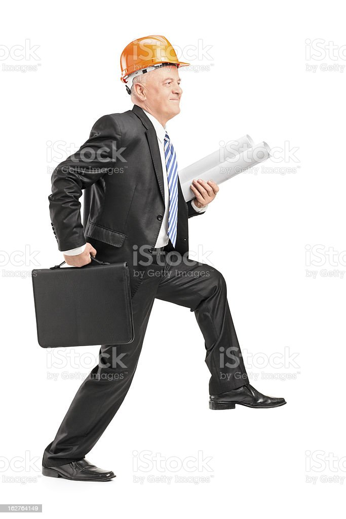 Male architect with helmet holding blueprints and suitcase royalty-free stock photo