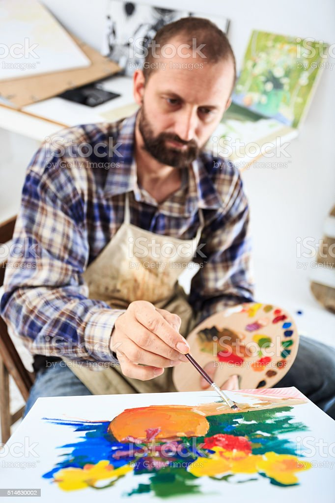 Male artist drawing in his studio stock photo