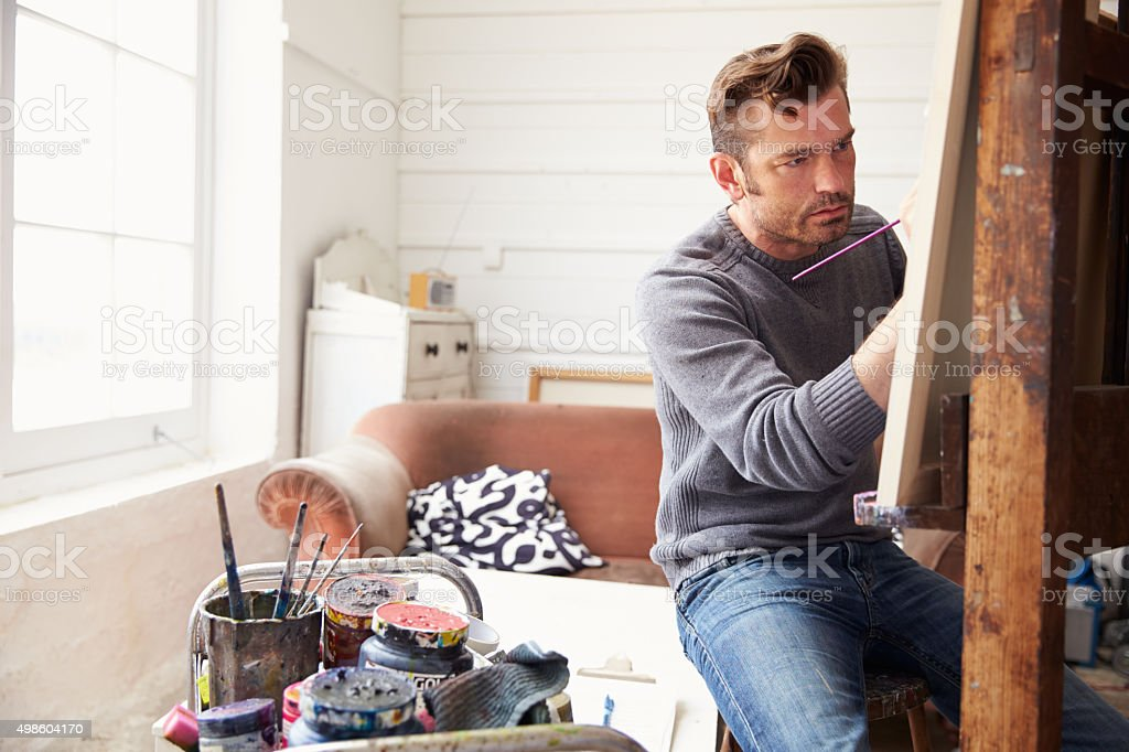 Male Artist Working On Painting In Studio stock photo