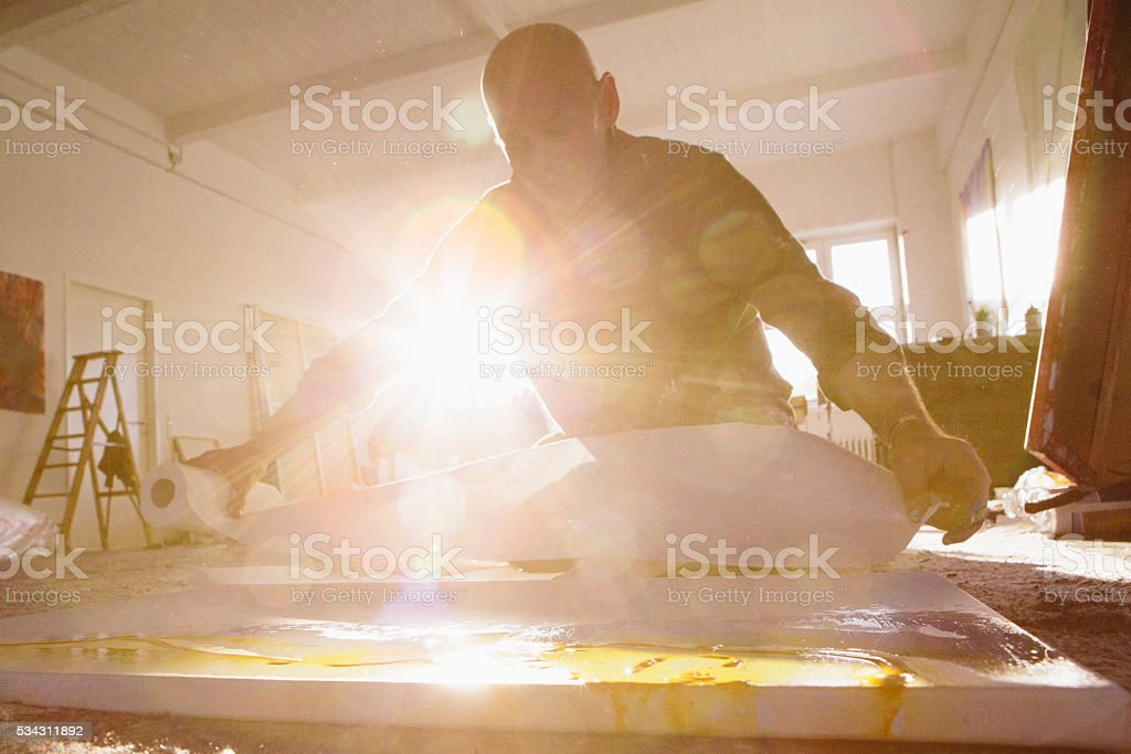 Male Artist works on his painting in his studio stock photo