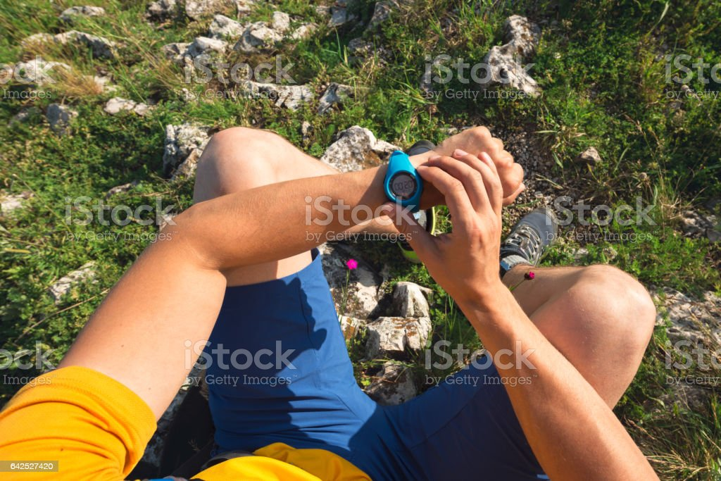 Male athlete checking his stopwatch after his workout stock photo