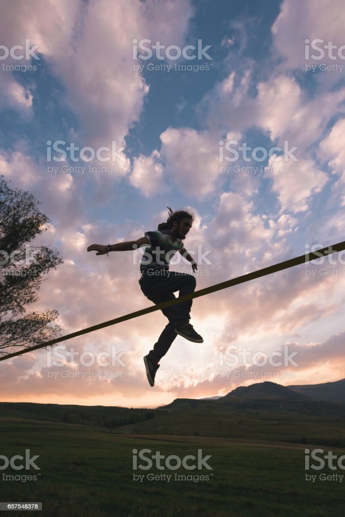 Male athlete doing extreme stunts on slackline rope outdoor in nature stock photo