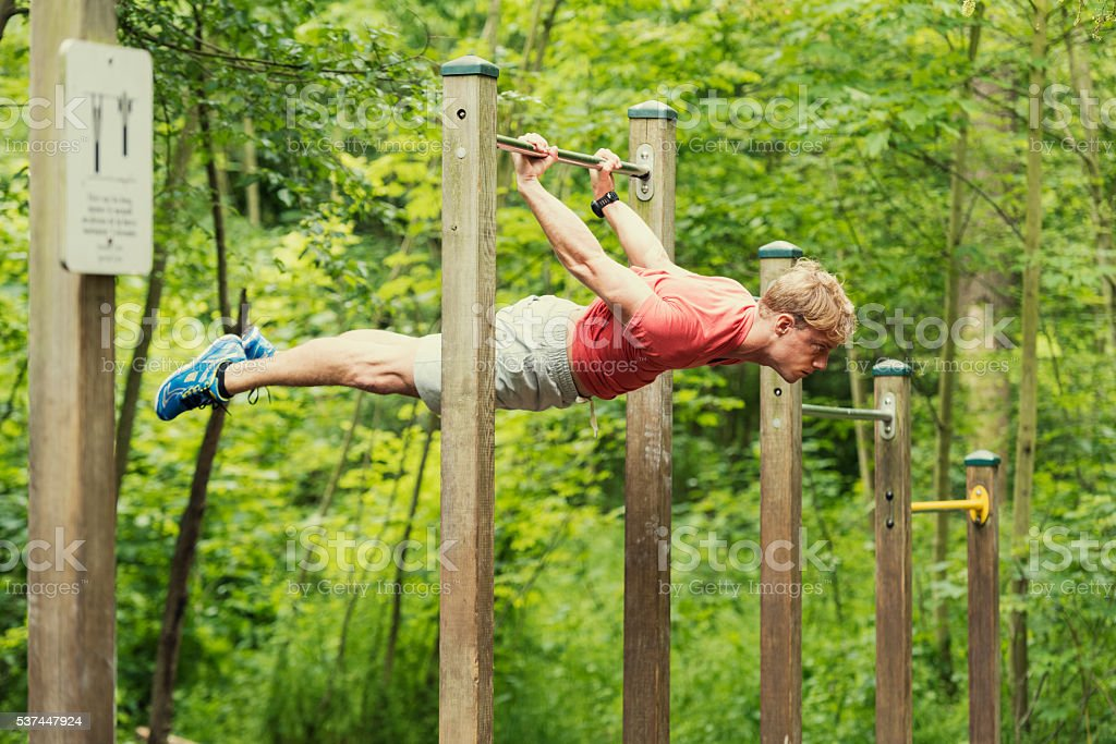 Male athlete doing muscle-up on horizontal bar stock photo