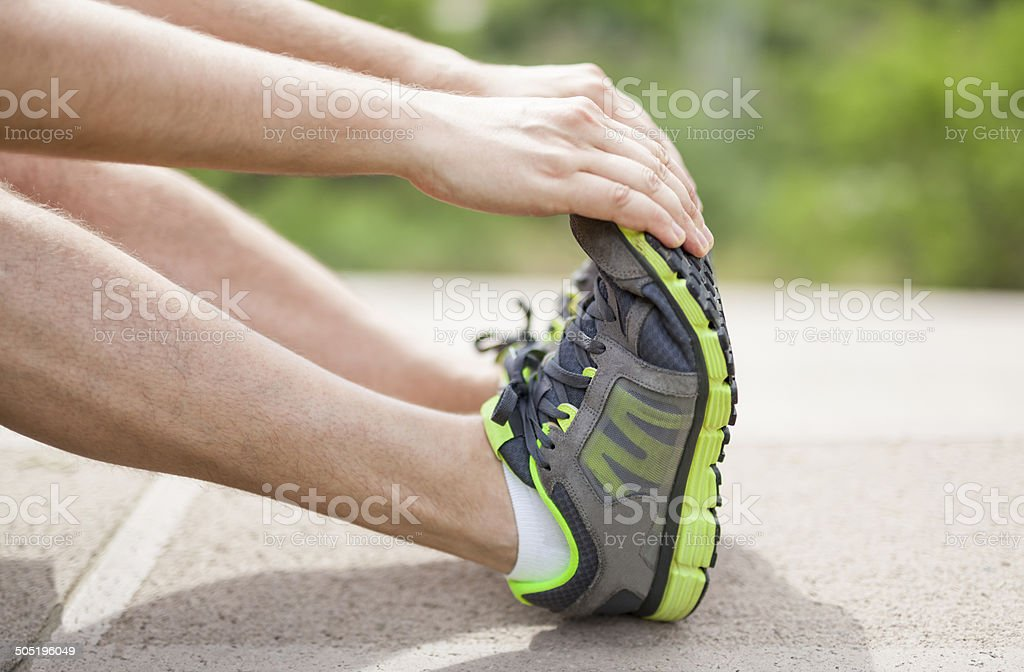 male athlete doing stretching exercise stock photo