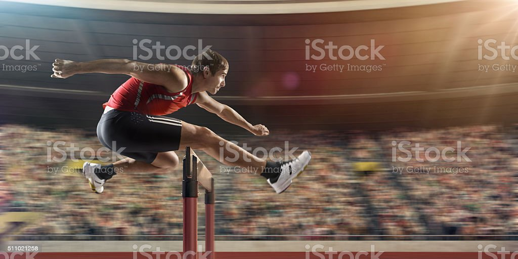 Male athlete hurdling on sports race stock photo